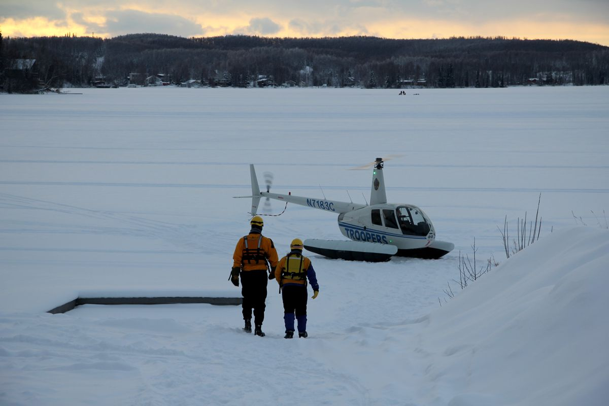 Members of the Mat-Su Borough Water Rescue Dive Team walk toward an Alaska State Troopers helicopter Friday on Big Lake as crews recover the body of missing snowmachiner LaVerne Pettigen. Crews found the body of Pettigen's husband nearby Saturday. (Alaska State Troopers)