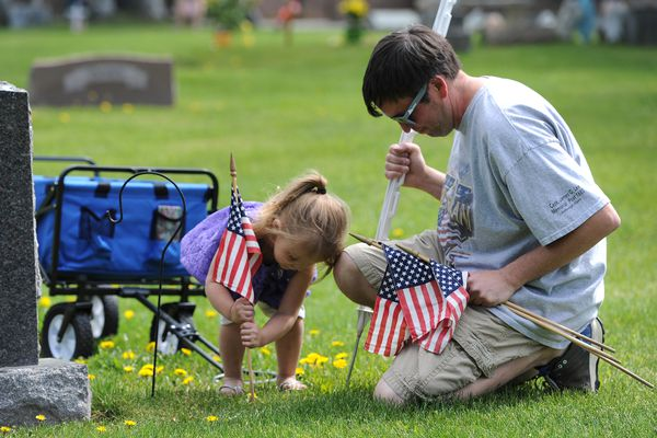 Two-year-old Dallas Pfouts and Danny Garcia along with volunteers from the Veterans of Foreign Wars Post 1685 in Spenard placed American flags at the graves of veterans resting in the Anchorage Memorial Park Cemetery on Sunday, May 29, 2016, in honor of Memorial Day on Monday. (Bill Roth / Alaska Dispatch News)