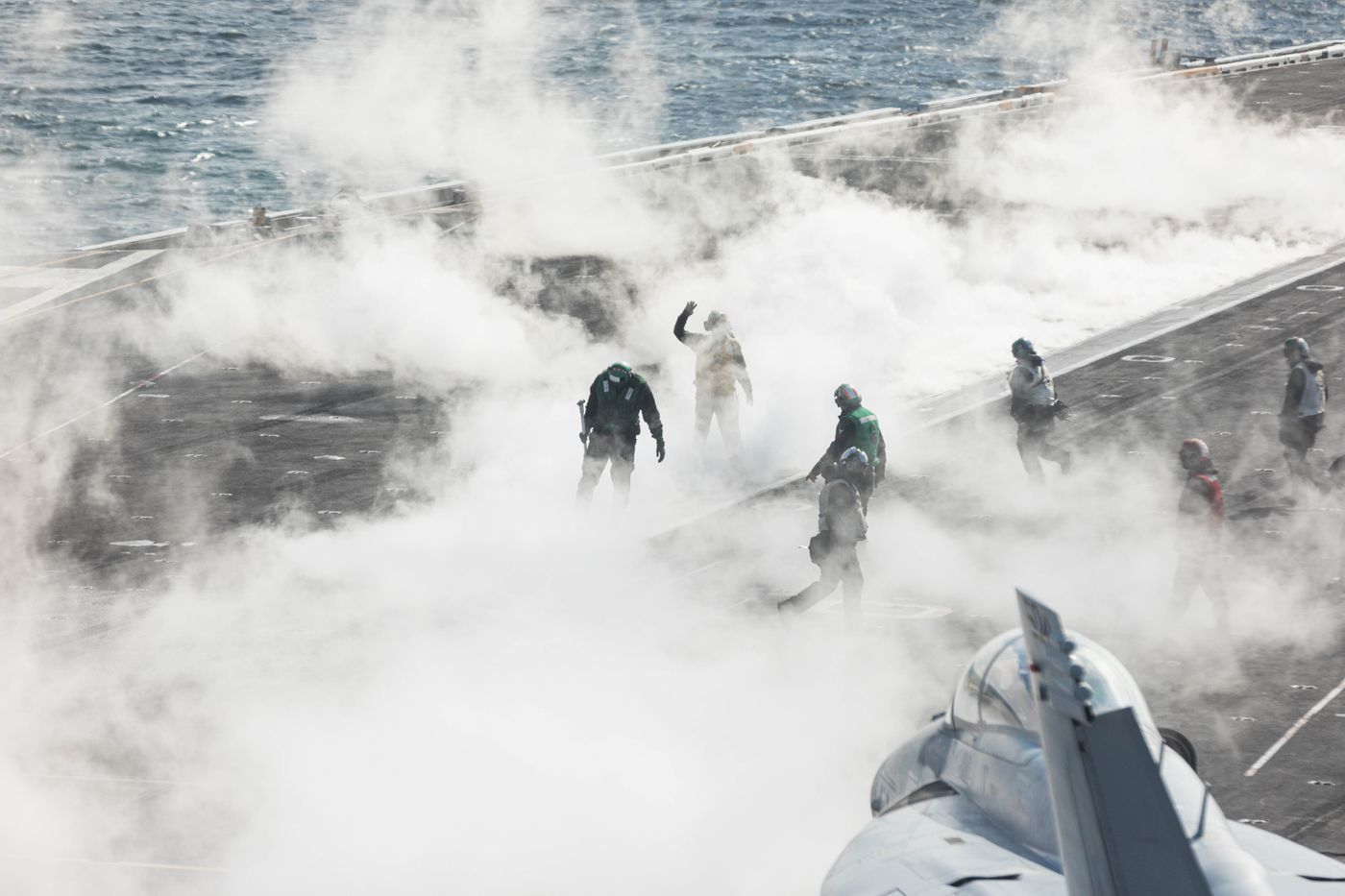 Flight deck crews walk through steam left over from the launch of a F/A-18 Super Hornet on Wednesday from the USS Theodore Roosevelt Nimitz-class aircraft carrier in the Gulf of Alaska south of Seward. The fighter jets are launched with the help of a steam-powered catapult, which can accelerate a 66,000 pound aircraft like a fully-loaded Super Hornet from 0-150 mph in under three seconds. (Loren Holmes / ADN)