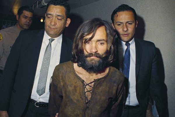 FILE - In this 1969, file photo, Charles Manson is escorted to his arraignment on conspiracy-murder charges in connection with the Sharon Tate murder case. Timing alone ensures that the Woodstock music festival and Charles Manson murders will be joined in memory. But the apex of peace and love and the abyss of pitiless violence were born out of similar drives as old as the U.S. itself. (AP Photo/File)