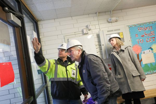 ASD's Thomas Fenoseff , Sen. Dan Sullivan, and ASD superintendent Deena Bishoplook at the wall of the gym at Eagle River Elementary School. The building was heavily damaged in the Nov. 30, 2018 7.0 earthquake. Photographed Dec. 4, 2018. (Loren Holmes / ADN)