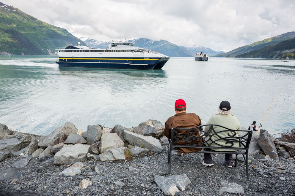 Tourists watch the Chenega fast ferry pulls into the dock in Whittier on Thursday, June 19, 2014. Departing is the ferry Aurora.