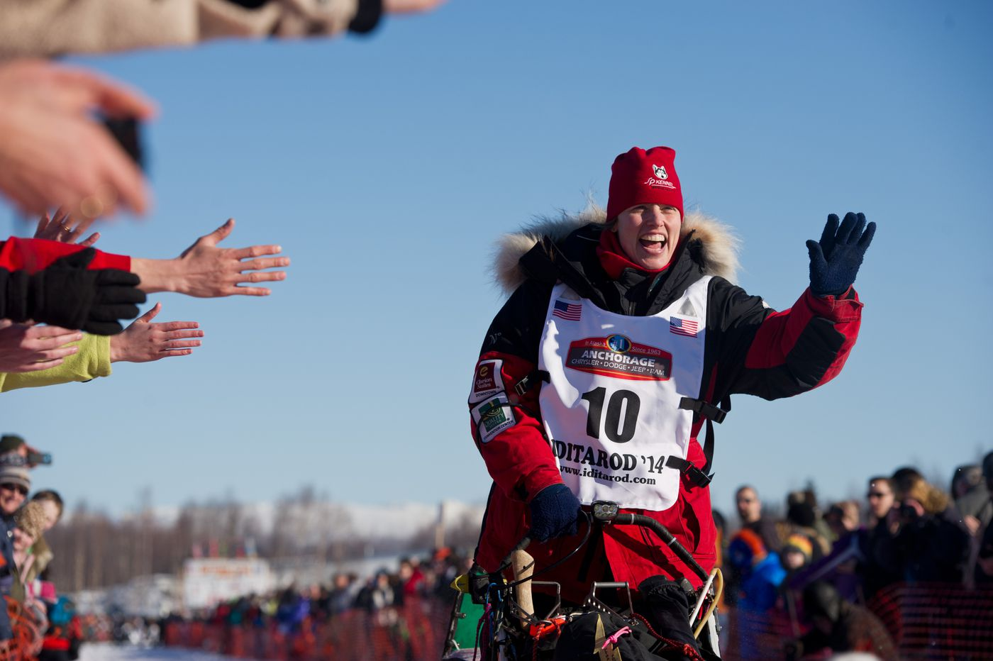 Aliy Zirkle waves to fans on Willow Lake at the start of the Iditarod on March 2, 2014. (Marc Lester / ADN archive)