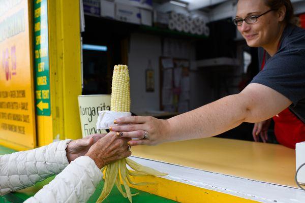 Nikki Blazka serves an ear of corn at Friar Tuck's Corn at the Alaska State Fair on August 28, 2018. (Marc Lester / ADN)