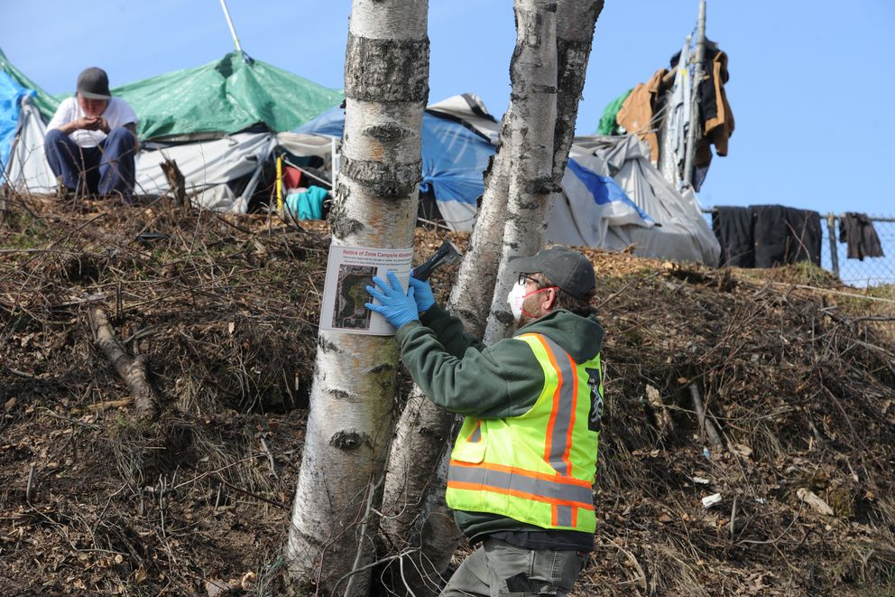 City Parks & Recreation worker Jamie Meeks posts an abatement notice as Anchorage police informed people at the illegal homeless camp at Third Avenue and Ingra Street on Thursday, April 30, 2020, that they should clear out before the camp is abated in 10 days. (Bill Roth / ADN)