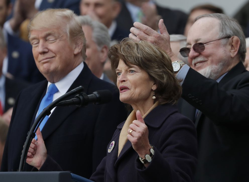 President Donald Trump stands with with Sen. Lisa Murkowski, R-Alaska, and Rep. Don Young, R-Alaska, as he celebrates with congressional Republicans after Congress passed sweeping tax overhaul legislation on the South Lawn of the White House in Washingtonon Wednesday. (REUTERS/Carlos Barria)