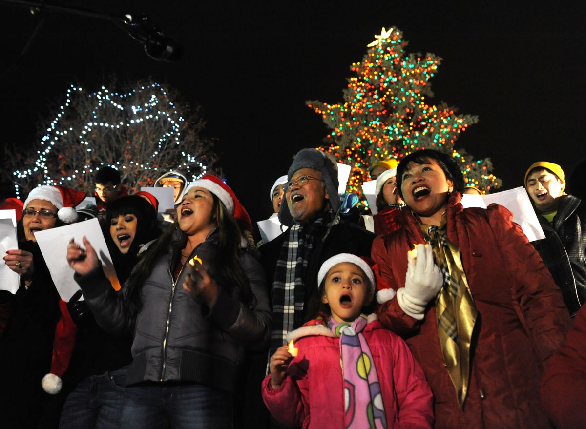The Philipino Community Choir sings with the Town Square Christmas tree in the background on Friday, November 28, 2014. The tree was lit by Santa Claus and 7 year old Sonia Marie Palesano during the AT&T Holiday Tree Lighting Ceremony. (Bob Hallinen / Alaska Dispatch News)