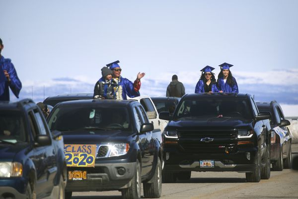 Kotzebue High School seniors stand in the beds of decorated trucks and wave to community members gathered along Third Avenue during a senior graduation parade in Kotzebue on Saturday, May 2, 2020. (Photo by Emily Mesner)