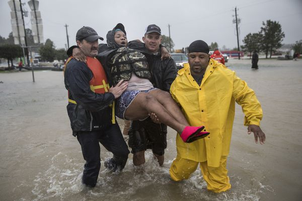 Karen Preston is carried to safety as she evacuates her neighborhood on the outskirts of Houston, Aug. 28, 2017. With record floodwaters devastating much of southeast Texas, more than 450,000 people are likely to seek federal aid in recovering from Harvey, the storm that has battered the Gulf Coast for days, a Federal Emergency Management Agency official said. (Tamir Kalifa / The New York Times)