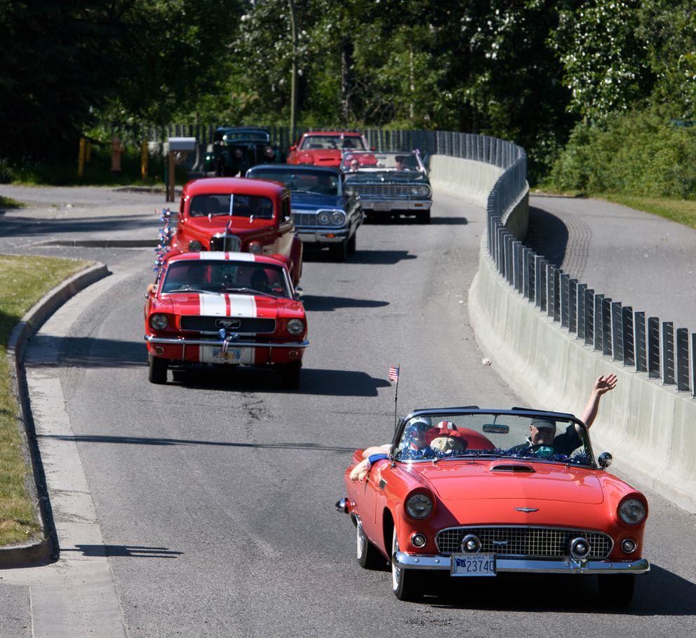 Antique Auto Mushers of Alaska president David Jensen waves as he passes in a 1956 Ford Thunderbird. (Marc Lester / ADN)