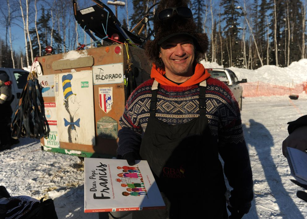 Hugh Neff shows the book he will carry to Nome for the Nome library. (Bob Hallinen / Alaska Dispatch News)