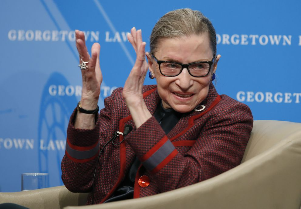 FILE - In this April 6, 2018, file photo, Supreme Court Justice Ruth Bader Ginsburg applauds after a performance in her honor after she spoke about her life and work during a discussion at Georgetown Law School in Washington. The Supreme Court says Ginsburg has died of metastatic pancreatic cancer at age 87. (AP Photo/Alex Brandon, File)