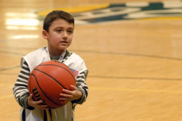 James Ludwig, 5, plays with a basketball on the court at the Alaska Airlines Center on Wednesday, Oct. 24, 2018. Ludwig, of Eagle River, suffers from epilepsy and recently signed on to become an unofficial member of the UAA men's basketball team through a partnership with Team IMPACT, a nationwide nonprofit. (Photo by Matt Tunseth)