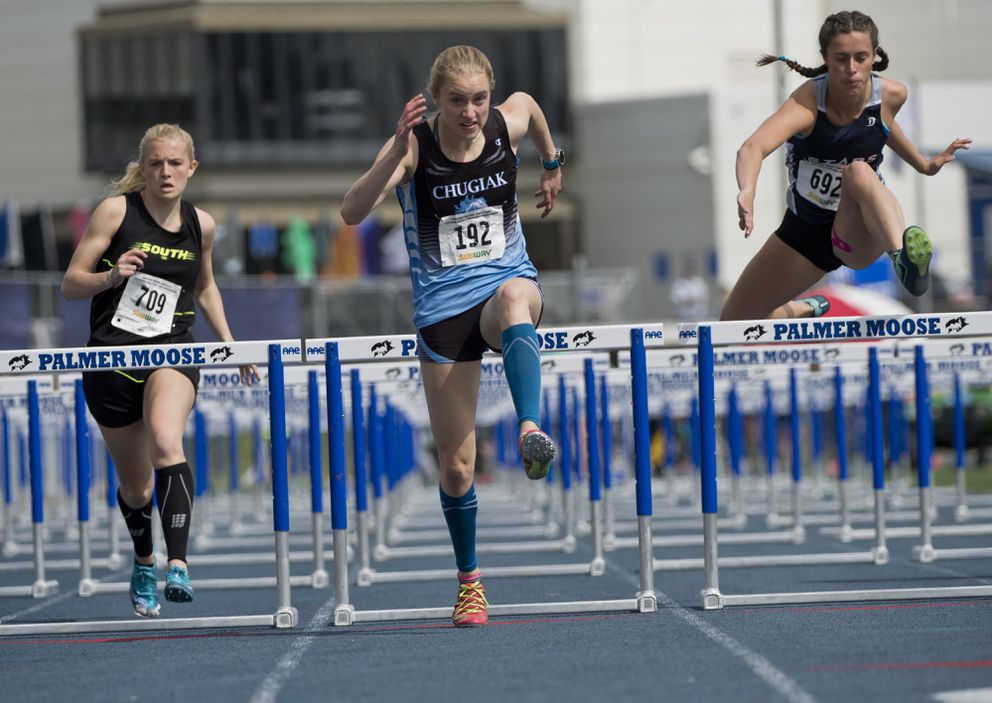 Chugiak's Brooklynn Gould, center, heads to the finish line in the 100-meter hurdles preliminaries on Friday. (Marc Lester / ADN)