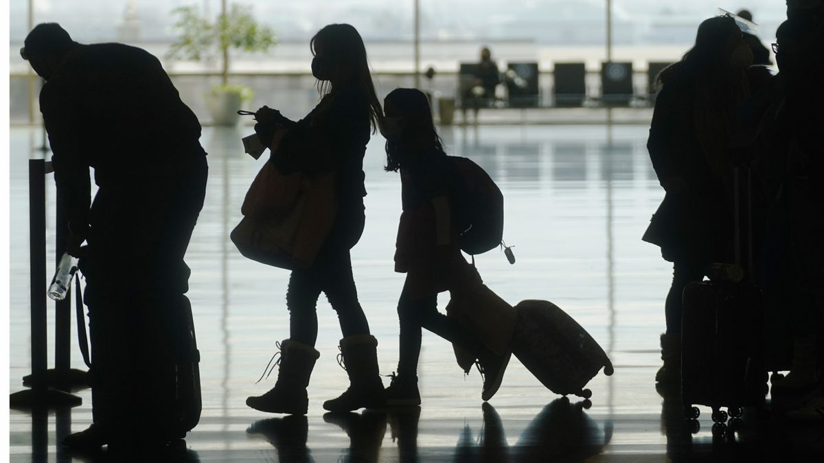 In this Wednesday, March 17, 2021, file photo, travelers walk through the Salt Lake City International Airport, in Salt Lake City. (AP Photo/Rick Bowmer, File)