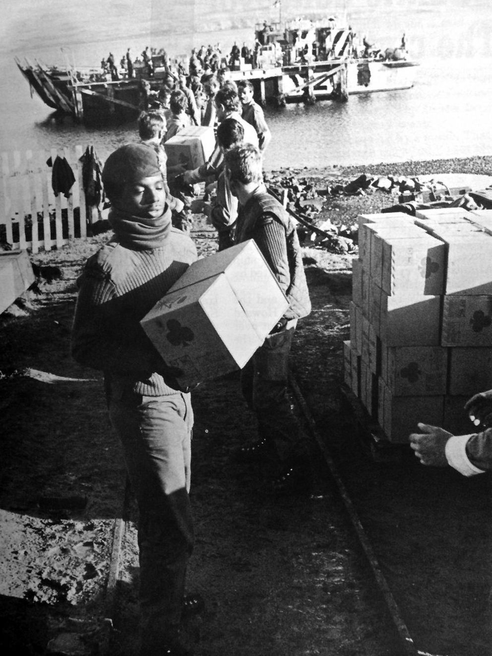 Royal Marines form a human chain to offload supplies in the Falkland Islands. Lack of infrastructure meant weapons and equipment loaded with forklifts and cranes in England had to be brought off the ships by hand. (Crown Copyright)