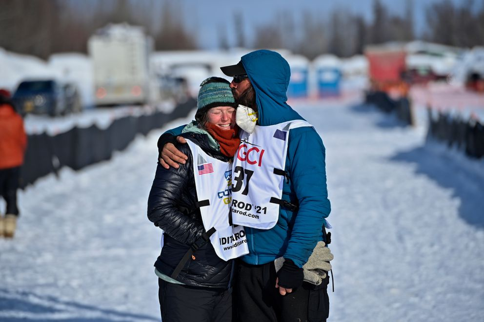 Paige Drobny gets a kiss from her husband Cody Strathe before they both left the Iditarod finish area in Willow on March 16, 2021. Drobny finished 19th and Strathe finished 20th in the 2021 Iditarod. (Marc Lester / ADN)