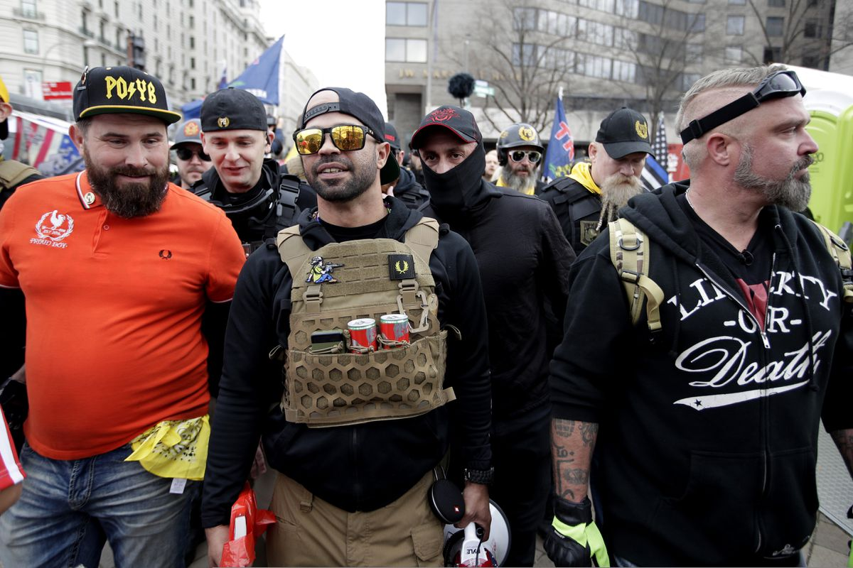 Supporters of President Donald Trump who are wearing attire associated with the Proud Boys watch during a rally at Freedom Plaza, Saturday, Dec. 12, 2020, in Washington. (AP Photo/Luis M. Alvarez)