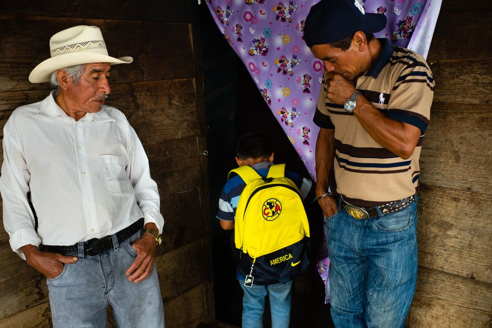 Marvel Carrillo, 5, center, shows his father's friends the Club America backpack he will use when he journeys through Mexico towards the United States. (Washington Post photo by Sarah L. Voisin)