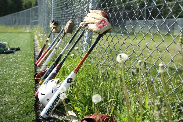 Baseball bats and gloves line the fence as players run drills. High school aged players attended the 22nd Annual College Coaches Clinic for the American Legion baseball players at Mulcahy Stadium on Wednesday June 17, 2015.