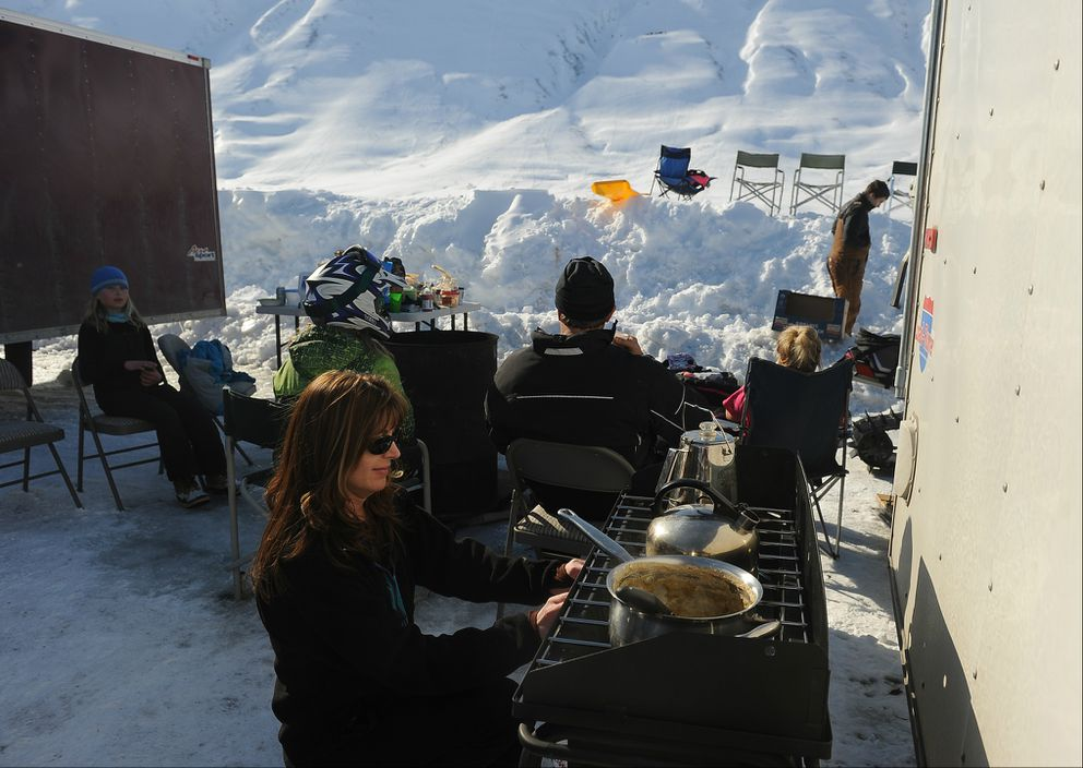 Sabnna Barber heats up soup as skiers and snowboarders on the east side of Turnagain Pass enjoy a warm spring day, April 2013. (Bob Hallinen / ADN archive)