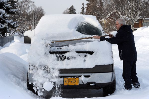 Phil Ramstad brushes about seven inches of snow off his pickup in the South Addition neighborhood near downtown Anchorage after the snowfall on Monday, March 2, 2020. Ramstad said he has lived in the neighborhood more than 80 years. (Bill Roth / ADN)
