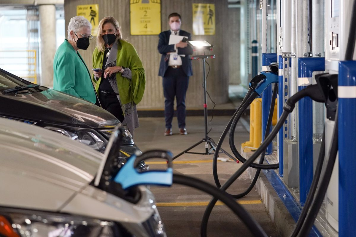 In this Thursday, April 22, 2021, file photo, White House climate adviser Gina McCarthy, left, talks with EVgo Chief Executive Officer Cathy Zoi, before the start of an event near an EVgo electric car charging station at Union Station in Washington. (Susan Walsh / AP)