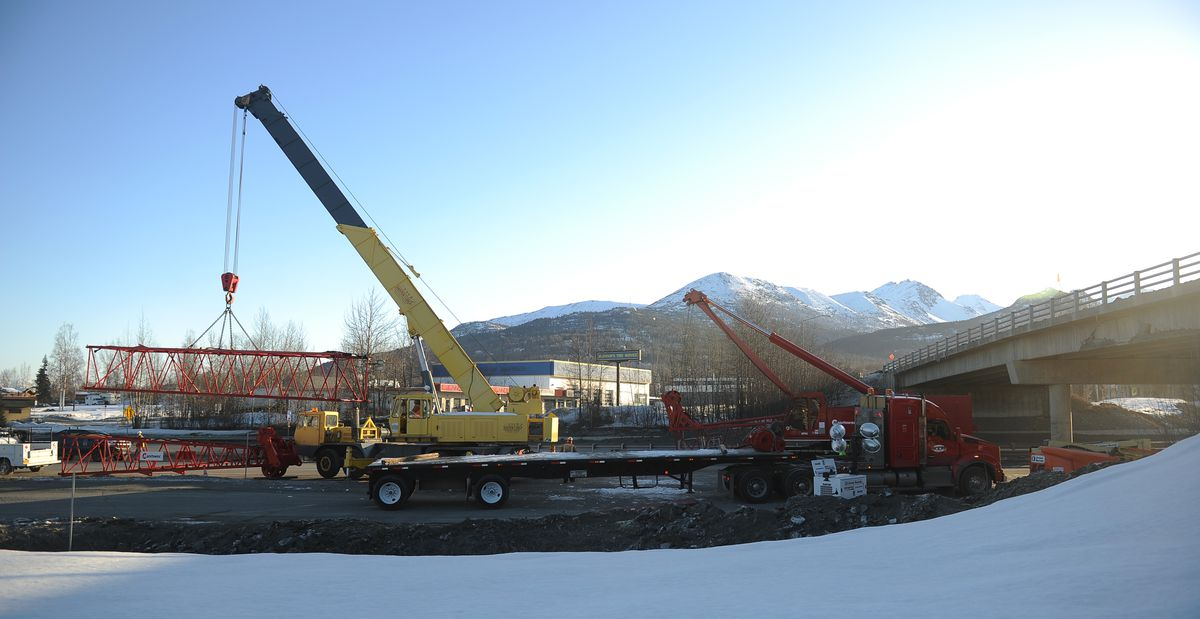 A section of crane derrick is unloaded from a flatbed trailer Friday at the Artillery Road overpass on the Glenn Highway as repairs get underway. (Bob Hallinen / ADN)