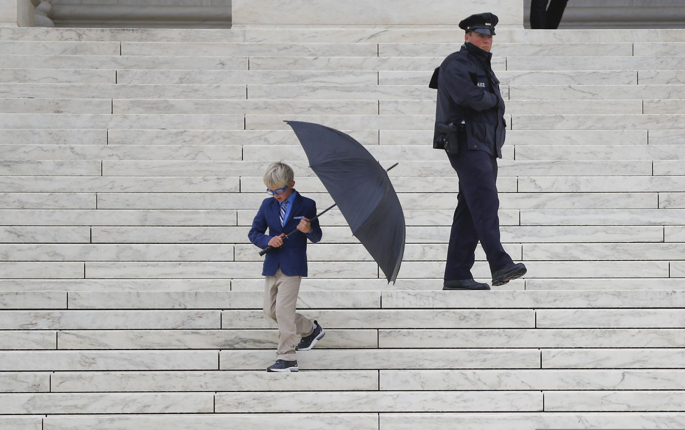 Matteo Halsey, 7, grandson of Alaska resident John Sturgeon walks down the stairs outside the Supreme Court, Monday, Nov. 5, 2018 in Washington. (AP Photo/Pablo Martinez Monsivais)