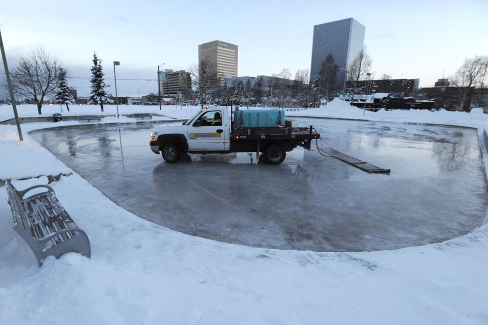 Parks and Recreation worker Fidelis Aki hot-mops the Delaney Park figure skating rink on Dec. 19. (Bill Roth / ADN)