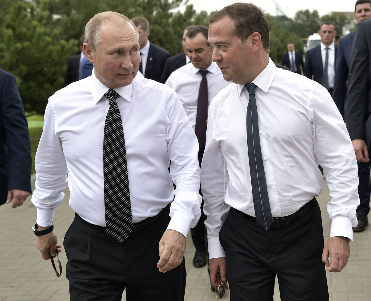 FILE In this file photo taken on Friday, Aug. 16, 2019, Russian President Vladimir Putin, left, and Prime Minister Dmitry Medvedev talk to each other as they visit the VolleyGrad Beach Sports Centre in Anapa, South Russia. Russian President Vladimir Putin prepares to mark his 20th year in power, as the longest-serving leader since Joseph Stalin. (Alexei Nikolsky, Sputnik, Kremlin Pool Photo via AP, File)