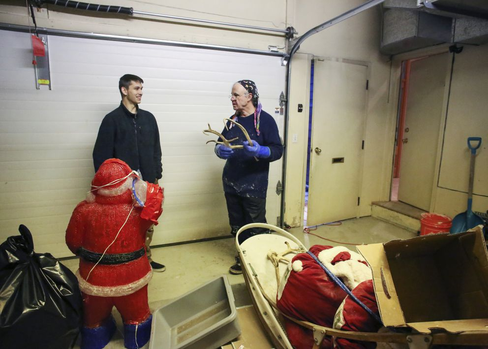 Tommy O'Malley shows Trace Edmundson his plan for decorating the ice sculpture they are working on in Anchorage on Friday, Dec. 4, 2020. (Emily Mesner / ADN)