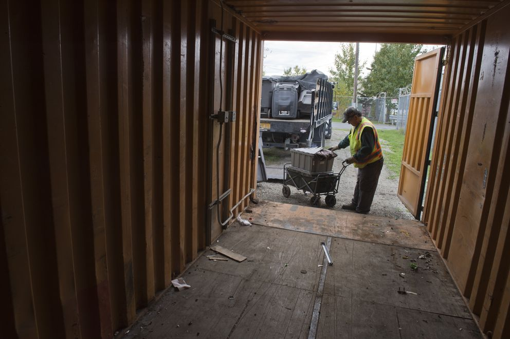 Parks and Recreation employee Manny Garcia loads belongings from a homeless camp into a cargo container at the Central Transfer Station on September 21, 2018.   (Marc Lester / ADN)