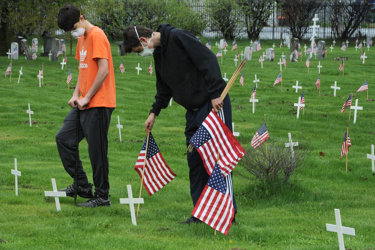 Alan Padgett, 14, left, makes a hole as his brother Ryan Padgett, 16, places a flag at Anchorage Memorial Park Cemetery on Sunday, May 24, 2020, in preparation for Memorial Day on Monday. Ryan said it's a way to 'remember the people who served.' (Bill Roth / ADN)