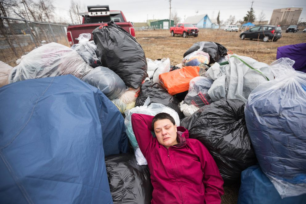 Amber Griffin lies on a pile of belongings removed from the homeless camp where she had been staying, near the Brother Francis Shelter. (Loren Holmes / ADN)