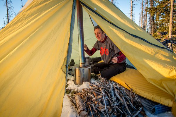 A camper stays warm inside his tent with a Titanium Goat WiFi wood stove. (Photo by Bjorn Olson)