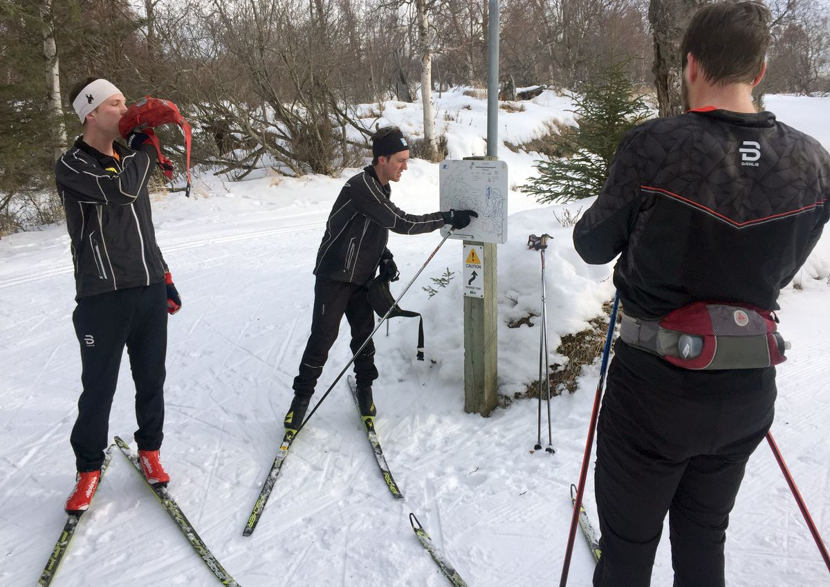 Cody Priest, center, consults a trail map at Kincaid Park as Peter Brewer, right, waits. Kyle Carpenter, left, joined the men for the Kincaid portion of their ski. (Photo by Allan Spangler)