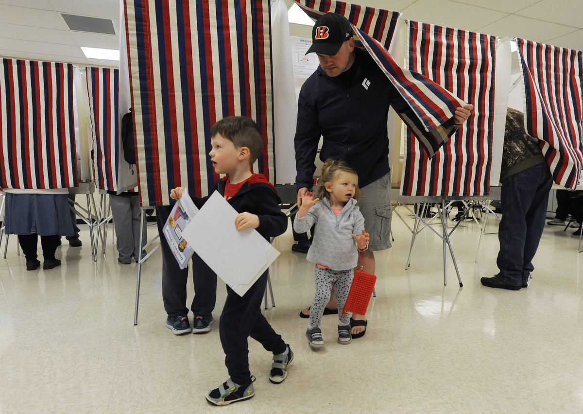 August Lambers, 3, carries a ballot as his sister Beatrice, 2, and father Jake Lambers exit the voting booth as early voting began for the general election on Monday, Oct. 22, 2018. (Bill Roth/ ADN)