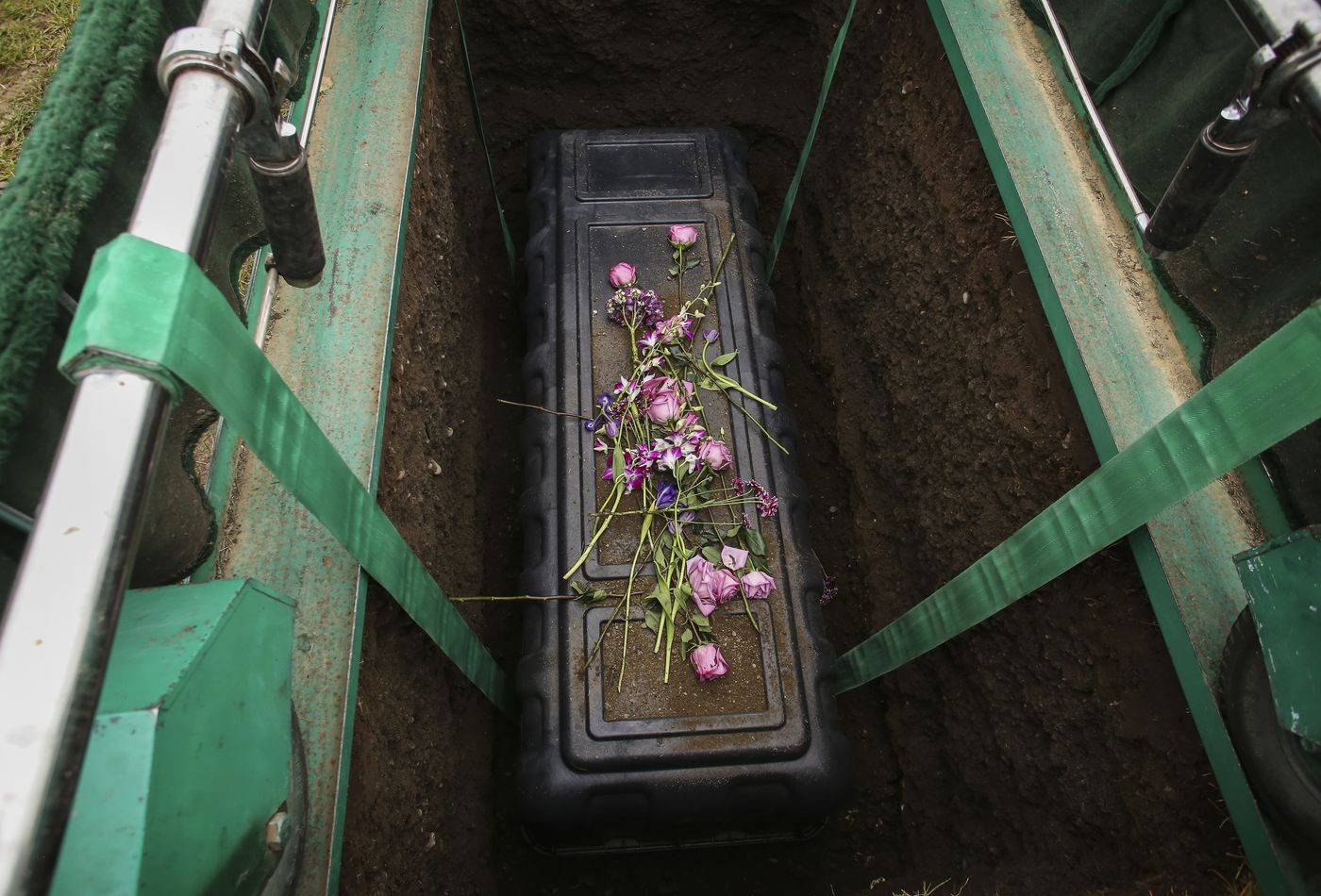 Pink roses and handfuls of dirt, tossed by family and friends, rest on the casket of Amanda Bouffioux during her burial on Tuesday. (Emily Mesner / ADN)