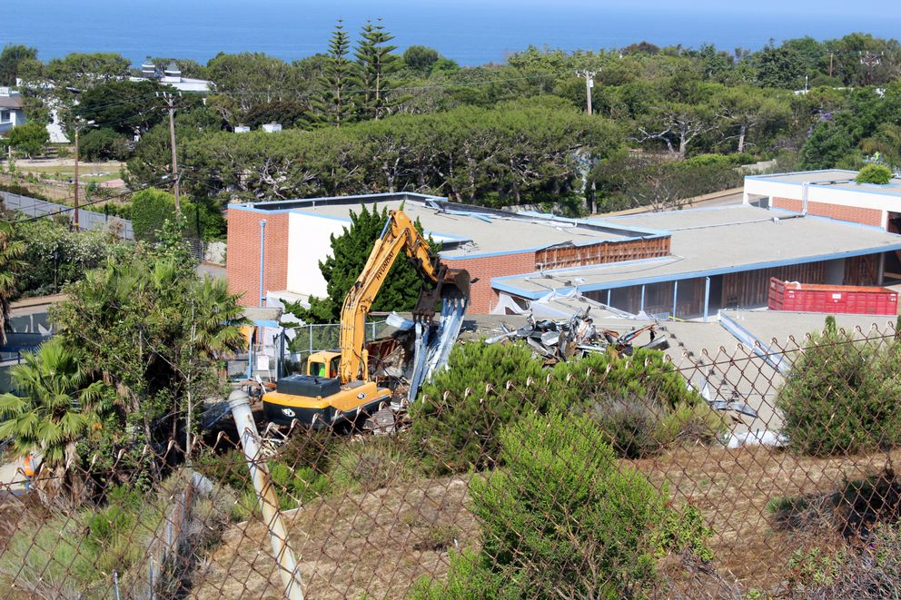 This July 5, 2017, image provided by Malibu Surfside News shows the demolition of the former Malibu Middle School in California. The school was torn down after testing found high levels of PCBs, which were used in some caulk, floor adhesive and in fluorescent light ballasts until the chemicals were banned in the late 1970s over fears that they could cause cancer. (Barbara Burke/Malibu Surfside News via AP)