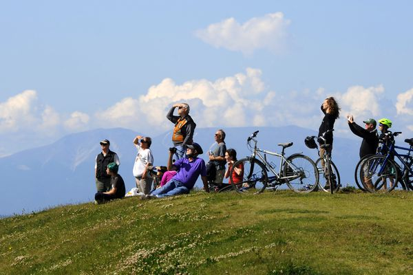 Cyclists pause along the Tony Knowles Coastal Trail to watch cargo planes take off from Ted Stevens Anchorage International Airport on Thursday, July 6, 2017, at Pt. Woronzof. (Erik Hill / Alaska Dispatch News)