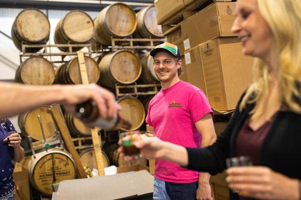 Big Swig Tours owner Bryan Caenepeel pours a glass of barrel-aged beer for Valerie Eubanks during a tour of King Street Brewing Company on Tuesday, June 26, 2018. Behind is King Street Brewing Company senior brewer Maxwell Crutch, who gave the three tour patrons a tour of the facility. (Loren Holmes / ADN)