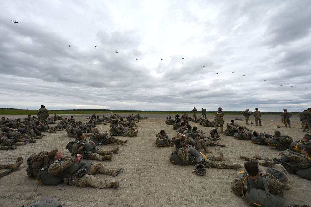 Paratroopers wait to jump as a line of paratroopers float to the ground on Tuesday. (Bill Roth / ADN)