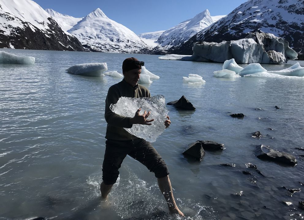 A barefoot Grant Gibbs carries an iceberg to shore at Portage Lake on Sunday, April 14, 2019. (Bill Roth / ADN)