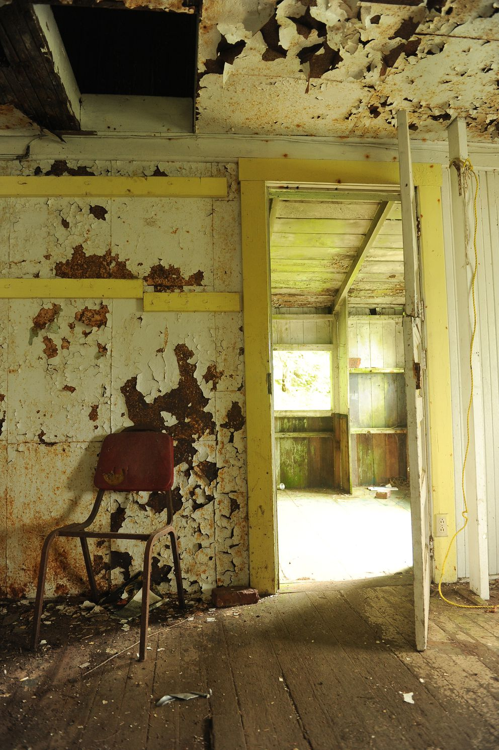Paint peels off the walls and ceiling in a cannery outbuilding. (Bob Hallinen / ADN)