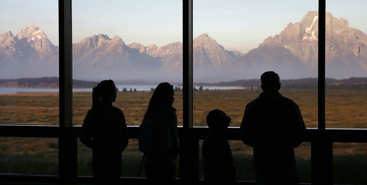 In this Aug. 28, 2016 file photo visitors watch the morning sun illuminate the Grand Tetons from within the Great Room at the Jackson Lake Lodge in Grand Teton National Park north of Jackson, Wyo. On Tuesday, March 24, 2020, the National Park Service announced that Yellowstone and Grand Teton National Parks would be closed until further notice, and no visitor access will be permitted to either park. (AP Photo/Brennan Linsley,File)