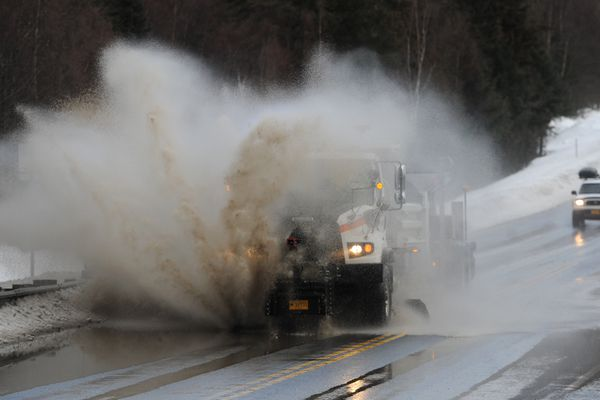 A plow truck busts through a puddle at mile 100.5 of the Seward Highway just south of Bird Creek as warm weather melts snow on Monday, Feb. 13, 2017. (Bill Roth / Alaska Dispatch News)