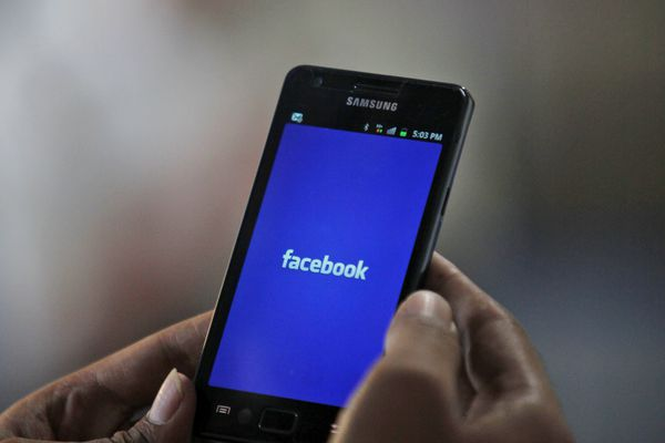 A man opens a Facebook page on his mobile phone in Hyderabad, India, Thursday, May 17, 2012. The company's shares are expected to begin trading on the Nasdaq Stock Market on Friday under the ticker symbol