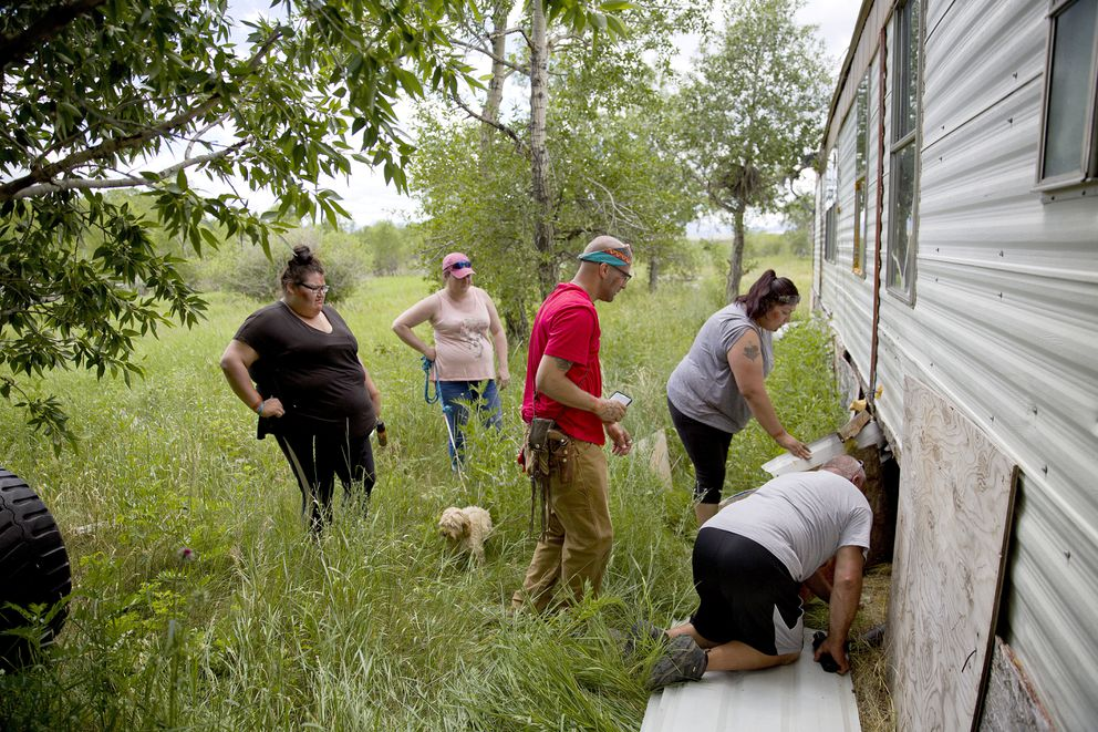 Kimberly Loring, from left, Staci Salois, Randy Ortiz, Lissa Loring and George A. Hall, look for clues under a trailer during a search in Valier, Mont., for the Loring's sister and cousin, Ashley HeavyRunner Loring, who went missing in 2017 from the Blackfeet Indian Reservation, Wednesday, July 11, 2018. Lissa says Ashley's disappearance constantly weighs on her. 'All that plays in my head is where do we look? Who's going to tell us the next lead? ' (AP Photo/David Goldman)