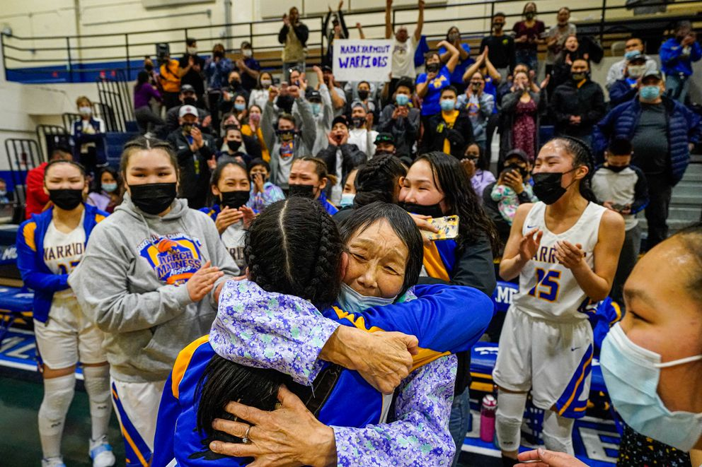 Gladys Hale-Abraham hugs members of the Hooper Bay girls basketball team after their 36-32 win over Su Valley on Saturday. Hale-Abraham's granddaughter Brandi Hale is the team's coach. (Loren Holmes / ADN)